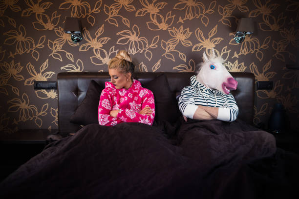unusual couple has relationship problems - unicorn bed imagens e fotografias de stock
