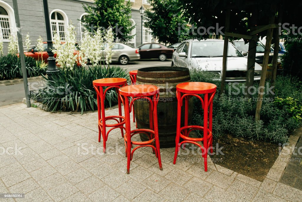 unusual red chairs and wooden barrel setting in street cafe creative service in Budapest & Unusual Red Chairs And Wooden Barrel Setting In Street Cafe Creative ...