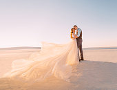Unusual wedding in the desert. A girl in a white dress ivory shade. Very long plume fluttering in the wind. A loving couple is embracing tenderly against the background of white sand and blue sky.