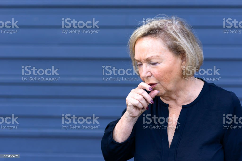 Unwell elderly lady having a coughing fit stock photo