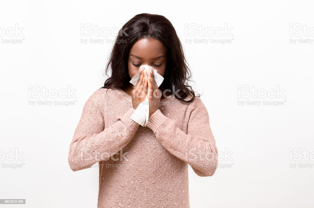 Unwell young woman blowing her nose stock photo