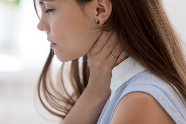 Unwell young woman touch neck suffering from angina Unhealthy young woman touch neck hard to swallow having discomfort or painful feeling, unwell sad female employee suffering from angina or tonsillitis, sore throat, experience loss of voice throat stock pictures, royalty-free photos & images