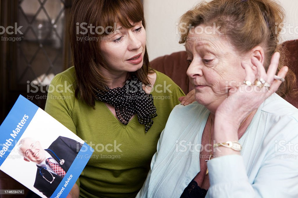 unwilling to quit smoking A look of reluctance on the face of a senior lady unwilling to quit smoking despite the protestations of her adult daughter.Property release provided for self-designed leaflet and visible artwork. 40-49 Years Stock Photo
