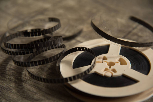 Unwound narrow retro film strip on a light reel on the background texture of the table. stock photo