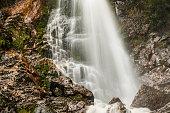 Up close idyllic flowing waterfall with moss and dense green rainforest environment, Tasmania, Australia