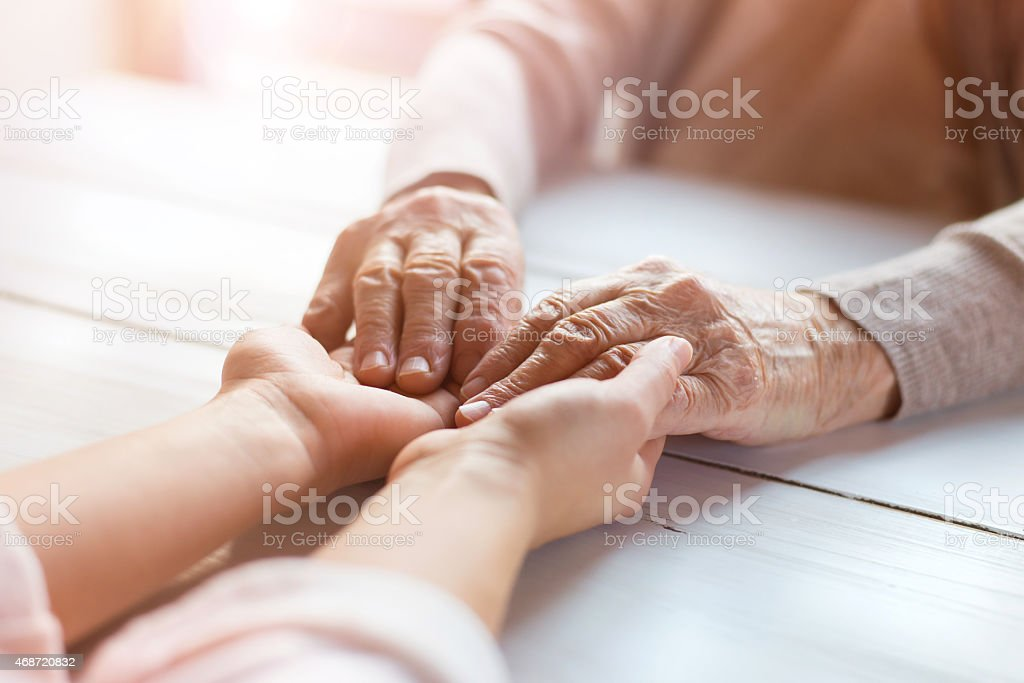 Up close photo of a senior woman's hands being held stock photo