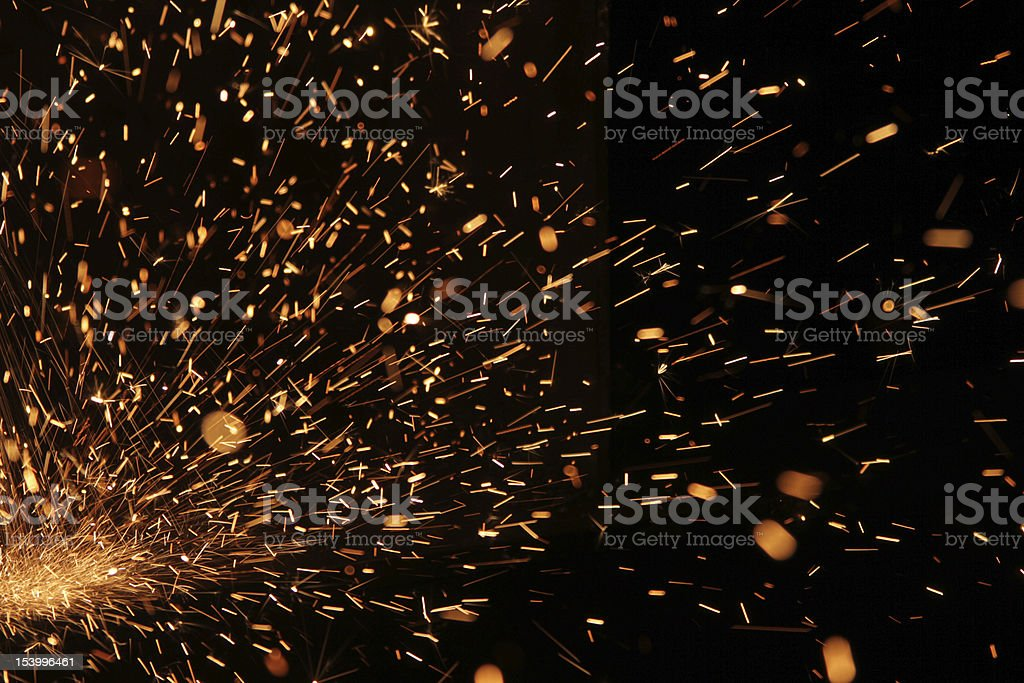 Up close photo of welding sparks flying through darkness stock photo