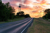 istock Up Hill Road Towards the Horizon With Water Tower Above the Trees in a Colorful Sunset 1250839841