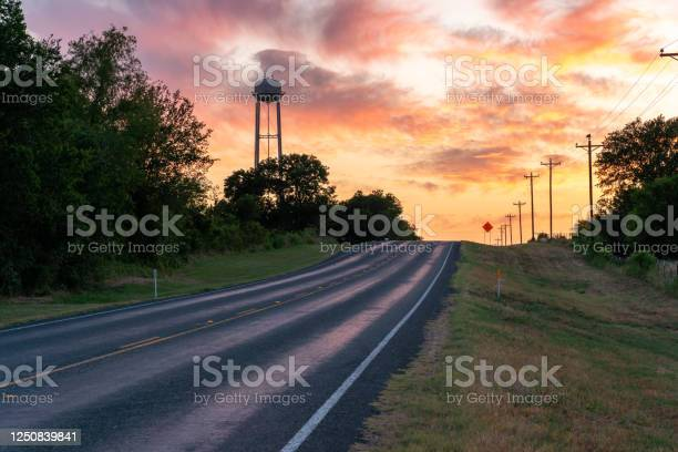 Photo of Up Hill Road Towards the Horizon With Water Tower Above the Trees in a Colorful Sunset