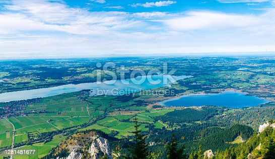 flying high over the beautiful Bavarian landscape during fall 2020, blue sky with some white clouds, enjoying the view over the lakes