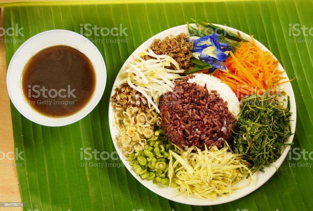 up Spicy Rice Salad with Vegetable and Budu Fish sauce southern style on banana leaf from top view prepare for serving , Thai traditional royalty-free stock photo