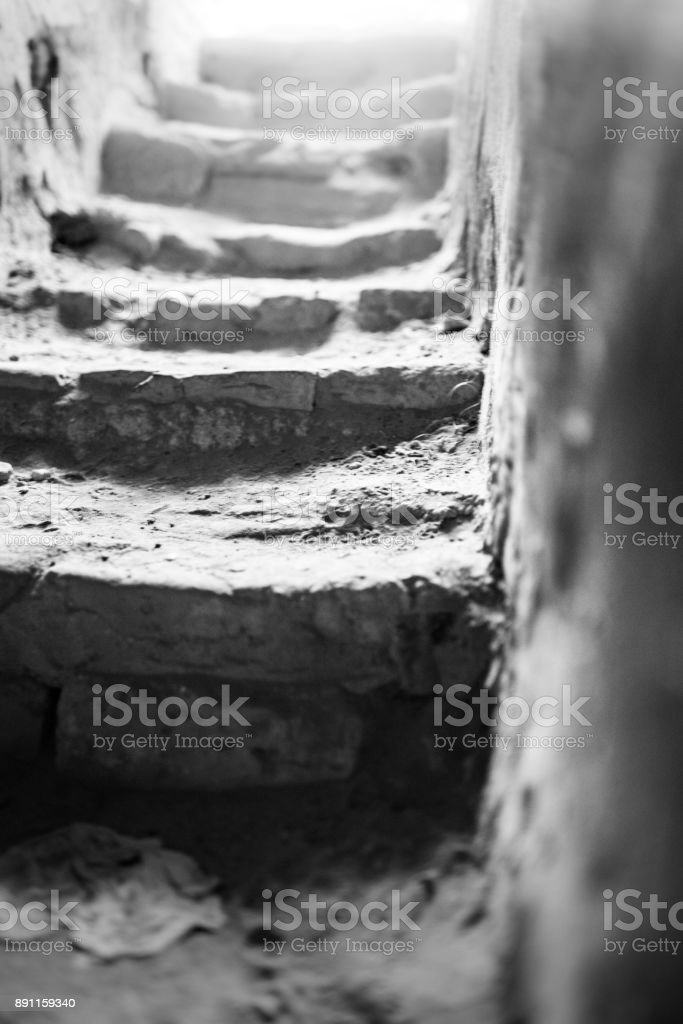 Up the rough stairs with light at the end of the tunnel stock photo