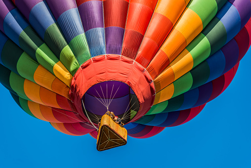 A hot air balloon flies by in the clear blue sky.