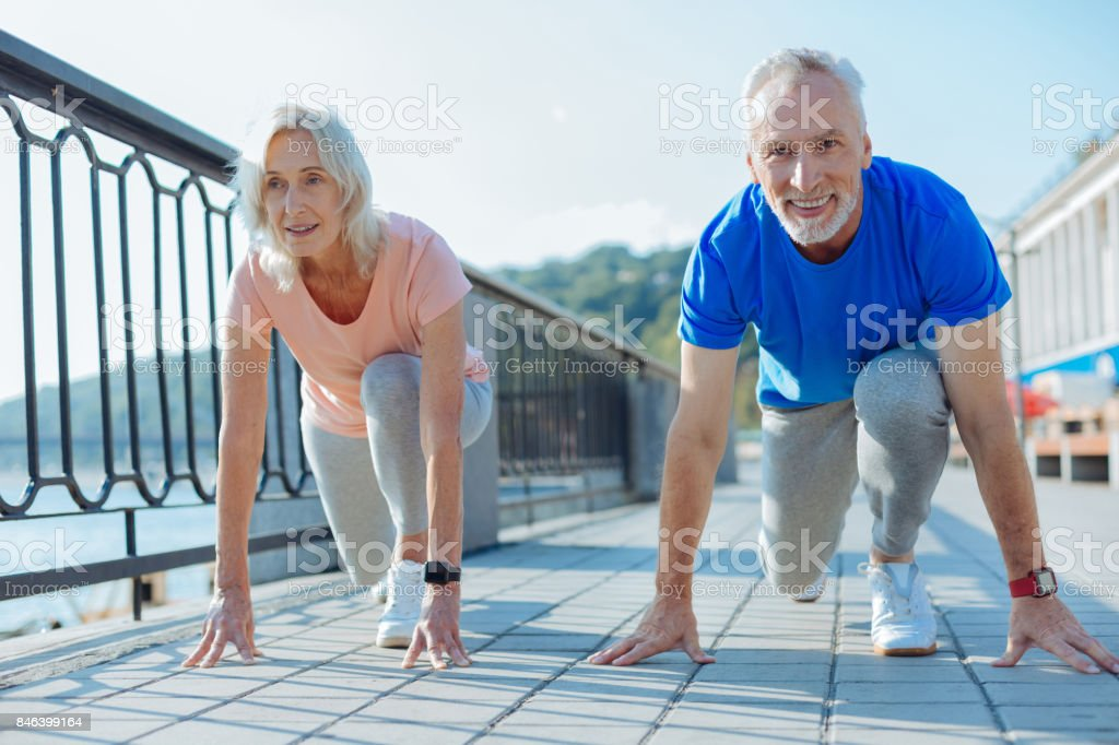 Upbeat elderly couple being about to start race - Foto stock royalty-free di Adulto in età matura