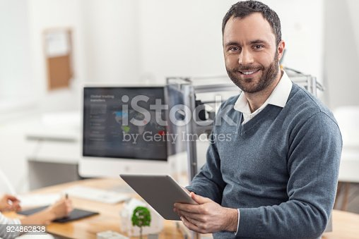 464482634istockphoto Upbeat man posing while reading from tablet 924862838