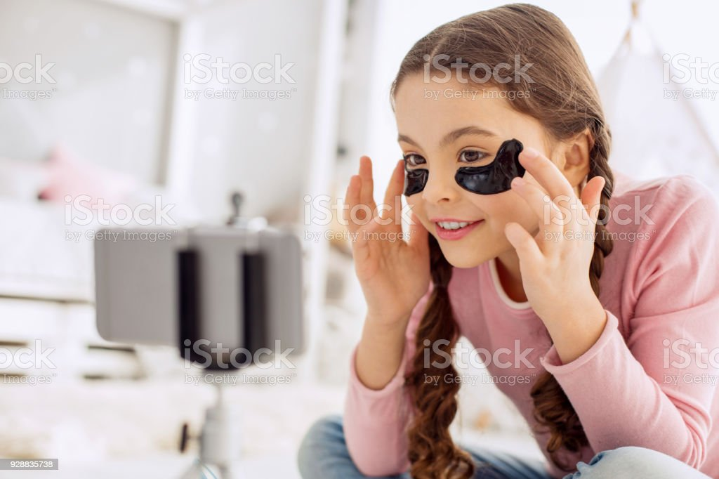 Upbeat pre-teen beauty blogger applying under-eye patches stock photo