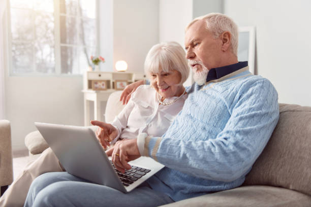 Upbeat senior couple doing online shopping together Doing everything together. Cheerful elderly couple sitting on the couch in the living room and choosing something from an online store while doing online shopping social security stock pictures, royalty-free photos & images