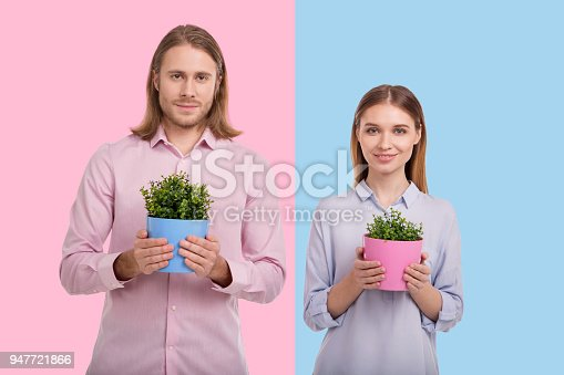 istock Upbeat young couple posing with flower pots 947721866