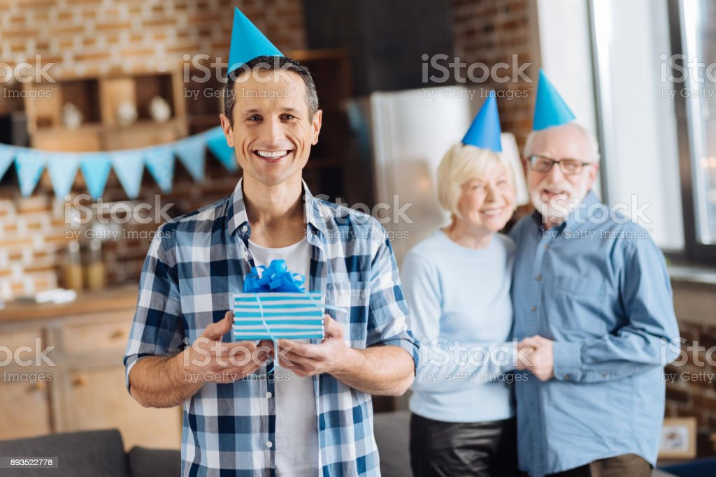Upbeat Young Man Holding His Birthday Present Royalty Free Stock Photo