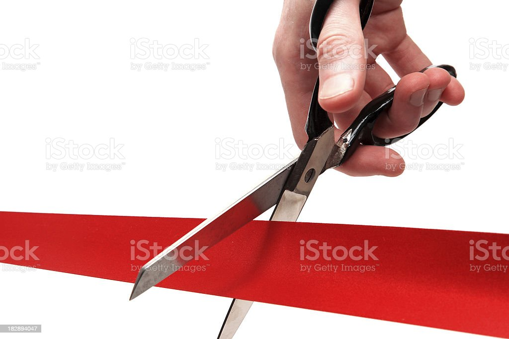 Up-close shot of scissors cutting through a red ribbon royalty-free stock photo