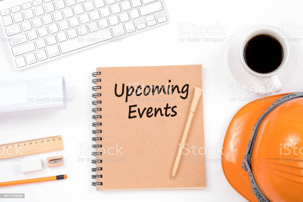 Upcoming Events concept. Top viwe of modern workplace with safety helmet, office supplies, a cup of coffee and keyboard on white background. stock photo
