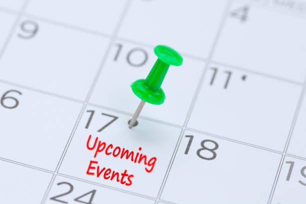Upcoming Events written on a calendar with a green push pin to remind you and important appointment. stock photo