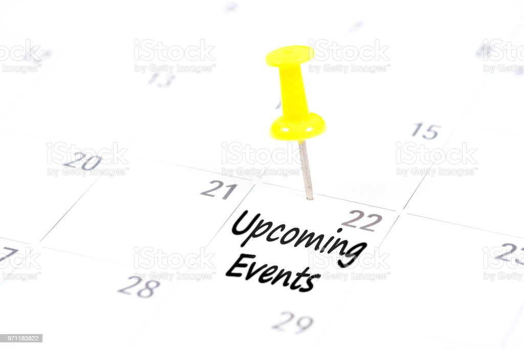 Upcoming Events written on a calendar with a yellow push pin to remind you and important appointment. stock photo