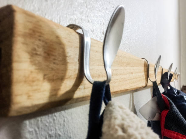 Upcycling coat hanger with spoons on wall stock photo