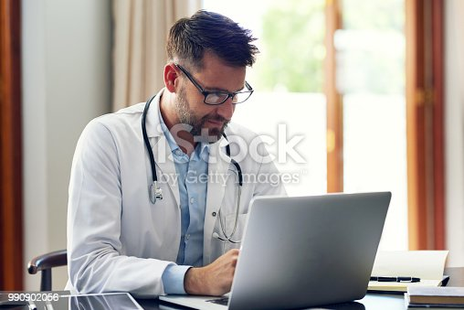 Cropped shot of a handsome male doctor working on his laptop while sitting in his office
