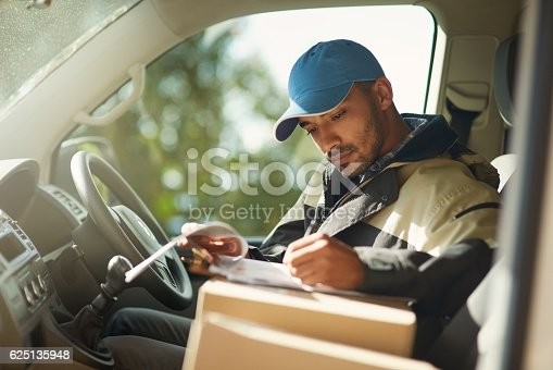 Shot of a delivery man reading addresses while sitting in a delivery van
