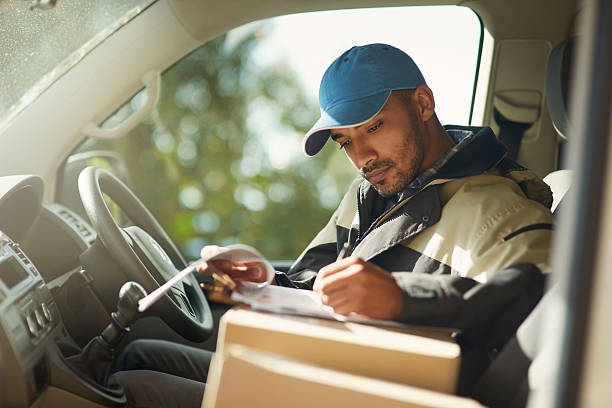 Updating his delivery status Shot of a delivery man reading addresses while sitting in a delivery van delivery man stock pictures, royalty-free photos & images