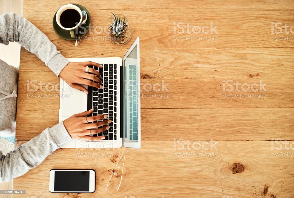 Updating my blog High angle shot of an unrecognizable businesswoman sitting indoors alone and using her laptop to blog Adult Stock Photo