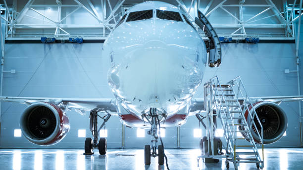 Up-Down Shot of a Brand New Airplane Standing in a Aircraft Maintenance Hangar. Plane's Door is Open and Ladder Stands Beside it. Up-Down Shot of a Brand New Airplane Standing in a Aircraft Maintenance Hangar. Plane's Door is Open and Ladder Stands Beside it. airplane hangar stock pictures, royalty-free photos & images