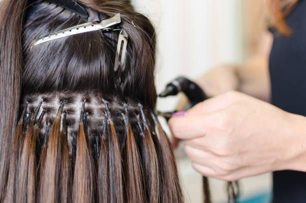 modernisierung der haare im salon - haarverlängerung stock-fotos und bilder