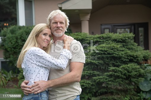 adult couple standing in front of their home