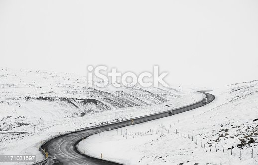 657042754 istock photo Uphill curve road with side way full of snow in winter 1171031597