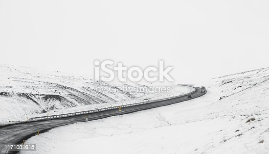 657042754 istock photo Uphill curve road with side way full of snow in winter 1171031615