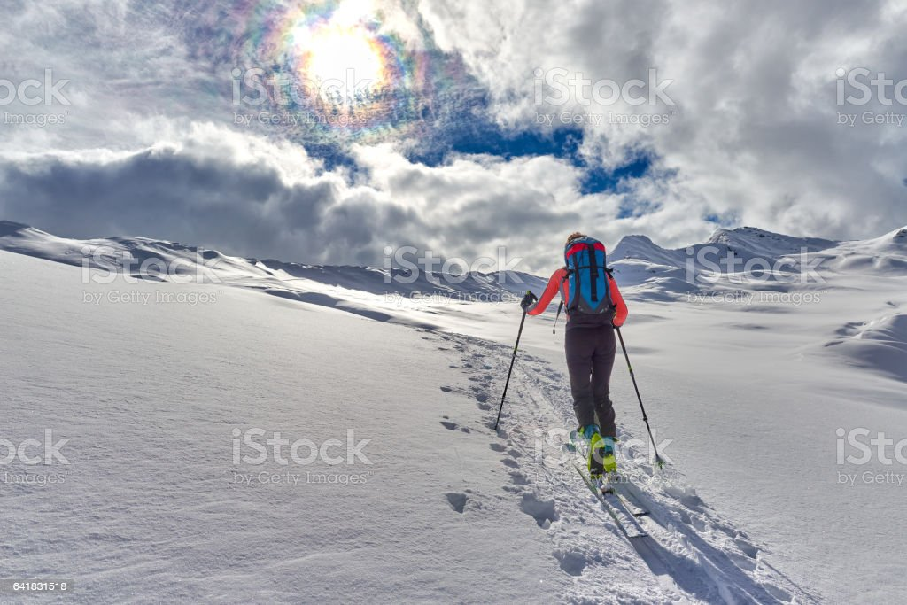 Uphill girl with seal skins and ski mountaineering stock photo