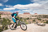A lonely female mountainbiker is struggeling uphill on the Ramblin Trail in the Navajo Rocks Trail Sytem (with Big Mesa, Monitor and Merrimac buttes in the background) nearby Moab which is a city on the southwestern edge of Grand County in eastern Utah in the western United States. Moab attracts a large number of tourists every year, mostly visitors to the nearby Arches and Canyonlands national parks. The town is a popular base for mountain bikers who ride the extensive network of trails including the Slickrock Trail, and for off-roaders who come for the annual Moab Jeep Safari.\nCanon EOS 5D Mark IV, 1/320, f/10, 24 mm.