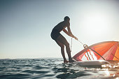 Low angle view of surfer silhouette balancing on windsurf board. Windsurfer uplift sail for windsurf sailing on sunset sea.