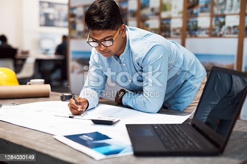 Shot of a young architect drawing up a building plan in a modern office