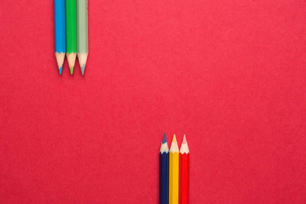 obere und untere reihen von bunten stiften in parallele position unten und oben auf dunklem rot papierhintergrund. business kreativität grafik design handwerk kinder schulkonzept. textfreiraum - unterrichtsplanung vorlagen stock-fotos und bilder