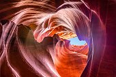 Turbulent waves of colorful sandstone created by natural erosion of Colorado Plateau enhances beauty of Antelope Canyon on Navajo Tribal Park near Page Arizona. Sunlight makes beautiful shadows