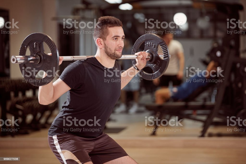 upper body shot, squat exercise, young man holding barbell with weights on back shoulders. Unrecognizable people behind in gym (out of focus) stock photo