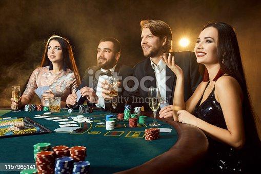 Upper class friends gambling in a casino. Two men in suits and two young women in dresses. Smoke. Casino. Poker