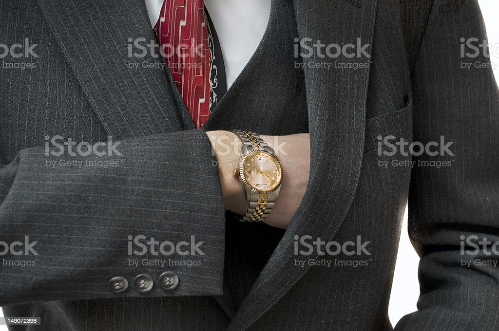 Upper class man reaching in pocket with gold watch stock photo