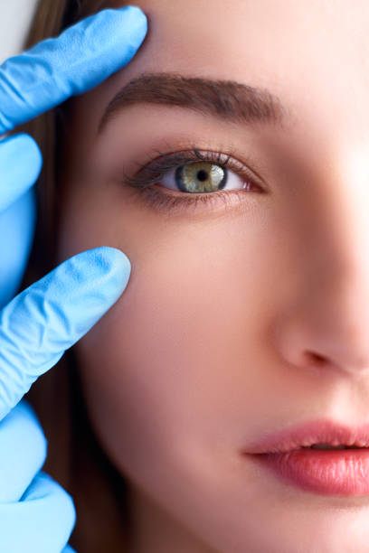 upper eyelid reduction, double eye lid removal plastic surgery concept. beautician doctor hands in gloves touching female face skin. ophthalmologist or oculist checks healthy vision in green eyesight - eyelid stock pictures, royalty-free photos & images