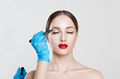 istock Upper eyelid reduction double eye lid removal plastic surgery cosmetic operation concept Woman eyes closed  doctor surgeon hand in gloves drawing cut line eyelid fat isolated white grey background 1204171330