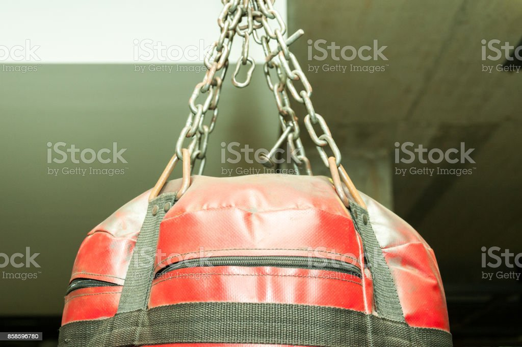 Upper part ob red punching boxing bag with chains closeup stock photo