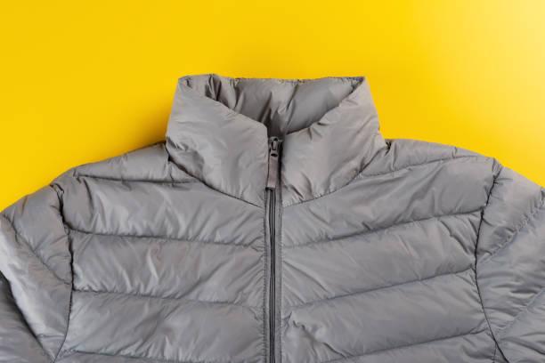 男性の上部は、黄色の背景にジャケットを絶縁ダウン - ダウンジャケット ストックフォトと画像